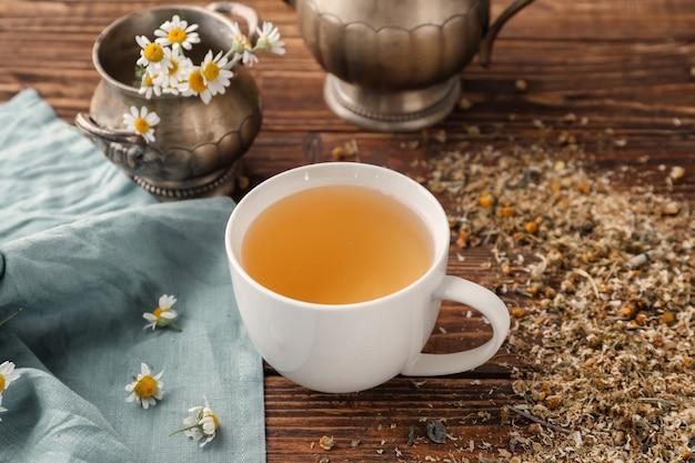 Xícara de chá de camomila delicioso na mesa de madeira