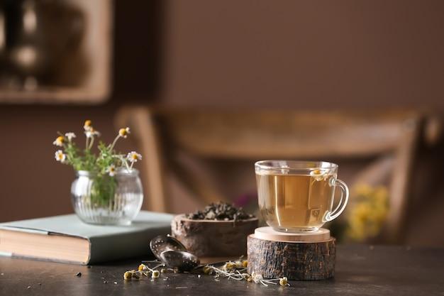 Xícara de chá de camomila delicioso na mesa