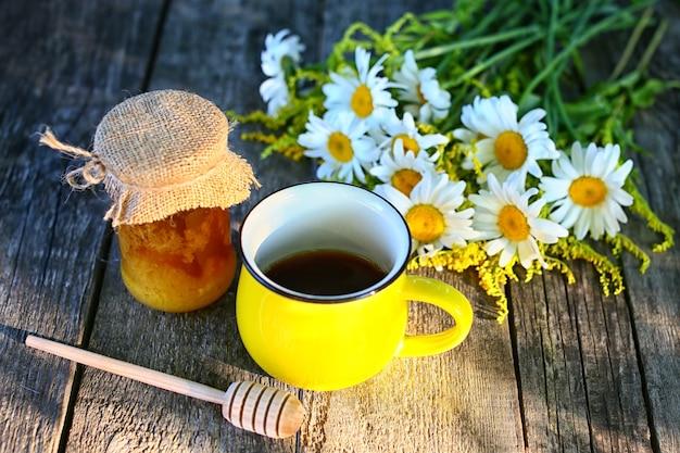 Xícara de chá de camomila e mel na mesa de madeira