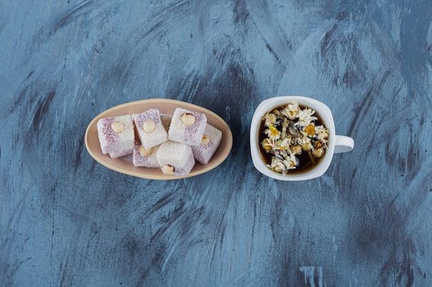 Xícara de chá de camomila e tigela de delícias de rosas sobre fundo azul.