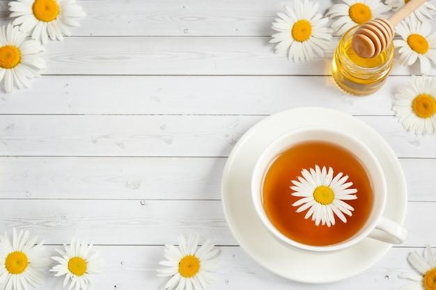 Xícara de chá de camomila em fundo branco de madeira
