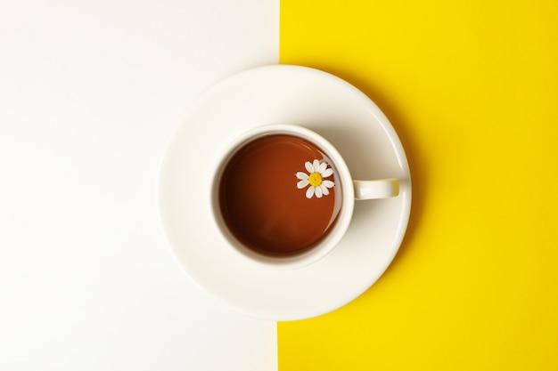 Xícara de chá de camomila em fundo de dois tons, vista superior