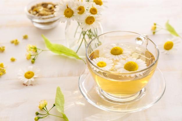 Xícara de chá de camomila quente na mesa de madeira