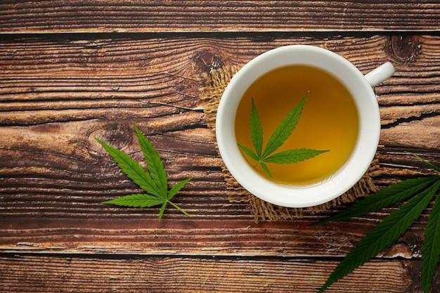 Xícara de chá de cânhamo com folhas de cânhamo colocada no chão de madeira