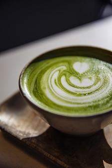 Xícara de chá de cerâmica branca na superfície marrom