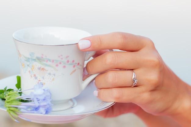 Xícara de chá de cerâmica com flores nas mãos bem cuidadas das mulheres com manicure.