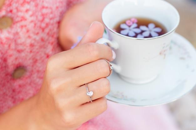 Xícara de chá de cerâmica nas mãos.