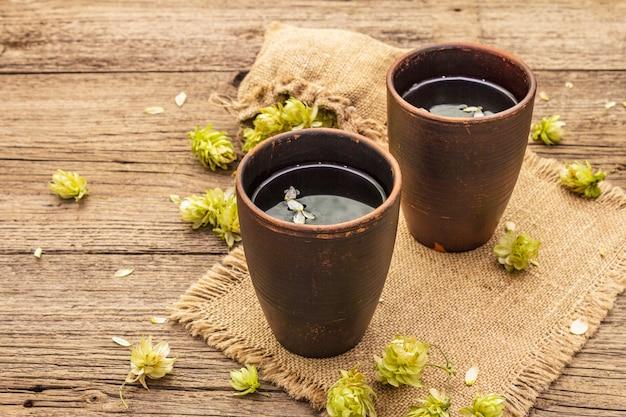 Xícara de chá de ervas calmantes com lúpulo selvagem fresco. cones de lúpulo no saco em placas vintage