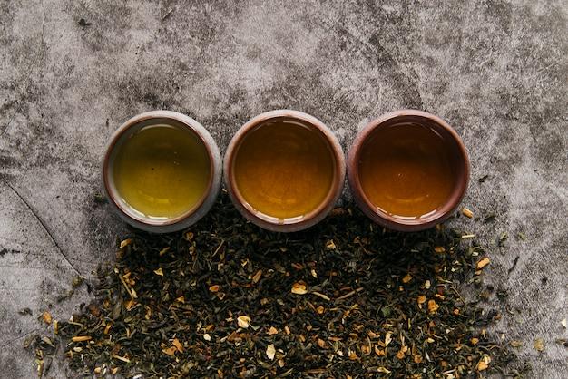 Xícara de chá de ervas chinesa com erva de chá seca em pano de fundo concreto