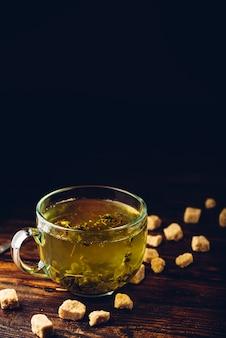 Xícara de chá de ervas com açúcar mascavo em uma superfície de madeira