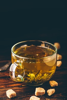Xícara de chá de ervas com açúcar refinado em um fundo de madeira