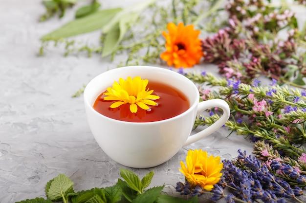 Xícara de chá de ervas com calêndula, lavanda, orégano, hissopo, hortelã e erva-cidreira sobre uma superfície de concreto cinza. vista lateral, foco seletivo.