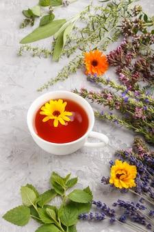 Xícara de chá de ervas com calêndula, lavanda, orégano, hissopo, hortelã e erva-cidreira, vista lateral.