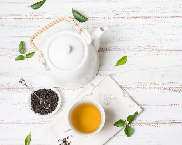 Xícara de chá de ervas com ervas secas e bule no plano de fundo texturizado branco