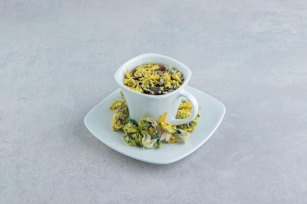 Xícara de chá de ervas com flores amarelas.