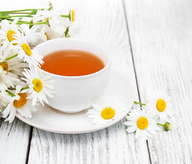 Xícara de chá de ervas com flores de camomila