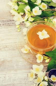 Xícara de chá de ervas com flores de jasmim. foco seletivo.