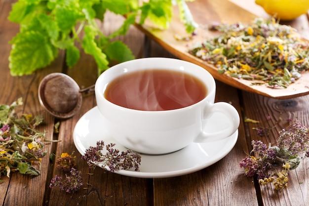 Xícara de chá de ervas com várias ervas na mesa de madeira