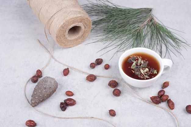 Xícara de chá de ervas, cranberries secas e pinha na mesa de mármore. foto de alta qualidade