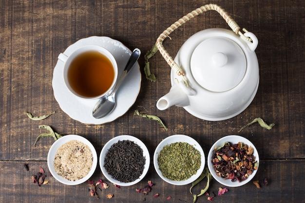 Xícara de chá de ervas e bule com tigelas de ervas de chá na mesa de madeira