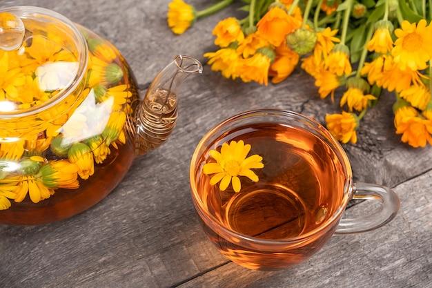 Xícara de chá de ervas e bule transparente e flores de calêndula na madeira