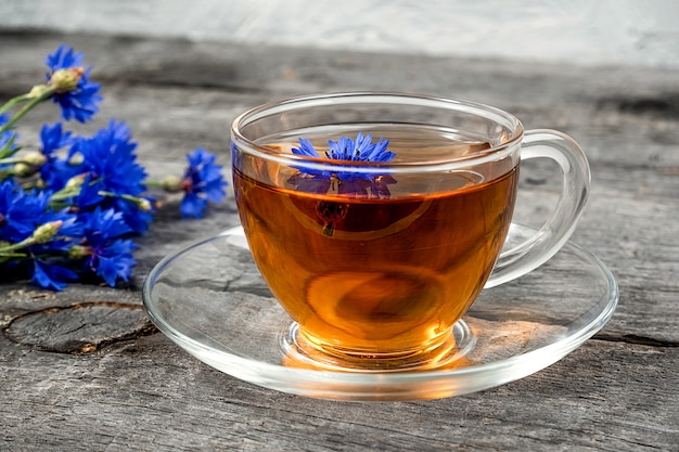 Xícara de chá de ervas e flores de centáurea azuis na superfície de madeira