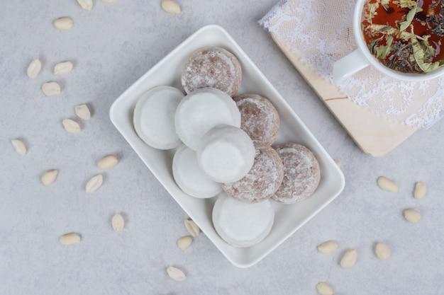 Xícara de chá de ervas e prato com vários biscoitos na placa de madeira. foto de alta qualidade