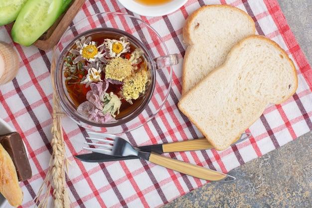 Xícara de chá de ervas, fatias de pão e talheres na toalha de mesa.