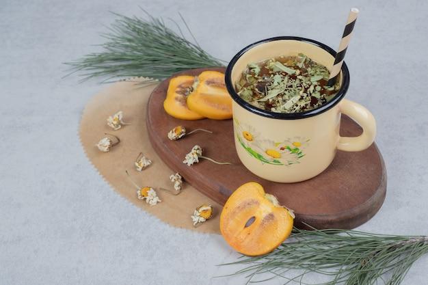 Xícara de chá de ervas, flores e fatias de caqui na placa de madeira. foto de alta qualidade