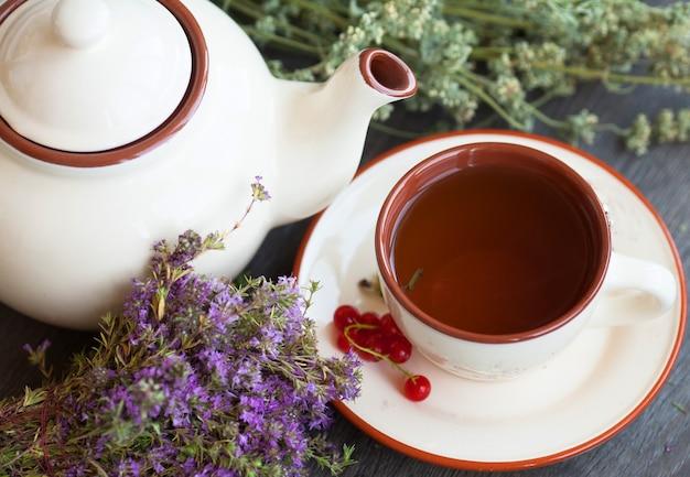 Xícara de chá de ervas na mesa de madeira