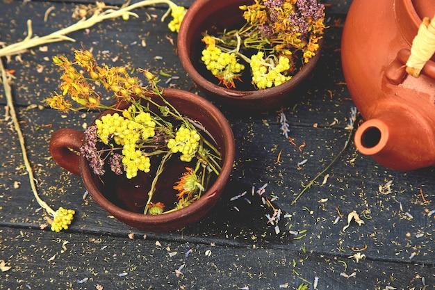 Xícara de chá de ervas - tutsan, sagebrush, orégano, helichrysum, lavanda perto de bule marrom em madeira escura. chá de ervas. ervas secas e flores, fitoterapia.