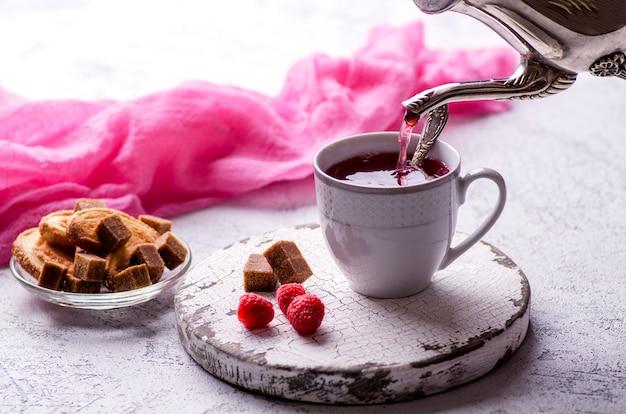 Xícara de chá de framboesa, cubos de açúcar e cookies. chave alta