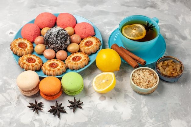 Xícara de chá de frente com biscoitos de macarons franceses e bolos na superfície branca biscoito biscoito bolo doce biscoito doce