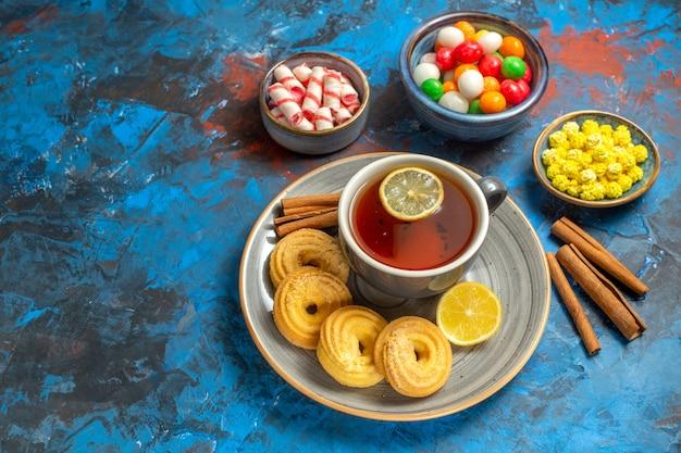 Xícara de chá de frente com biscoitos e doces na mesa azul chá de doces de biscoito
