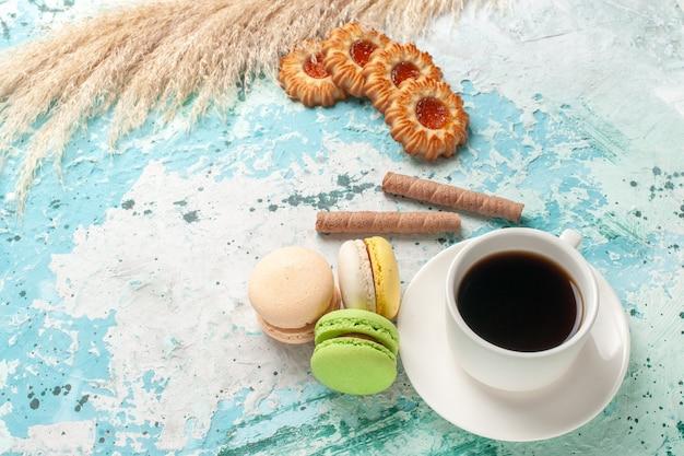 Xícara de chá de frente com biscoitos e macarons no bolo de superfície azul torta doce de biscoito
