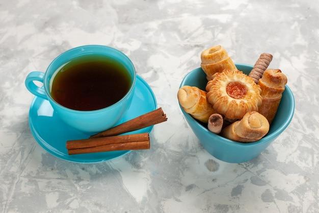 Xícara de chá de frente com biscoitos e rosquinhas no biscoito de torta de bolo de superfície branca