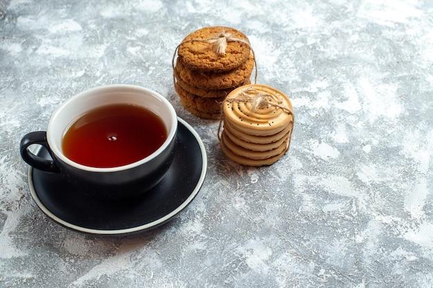 Xícara de chá de frente com biscoitos em fundo claro
