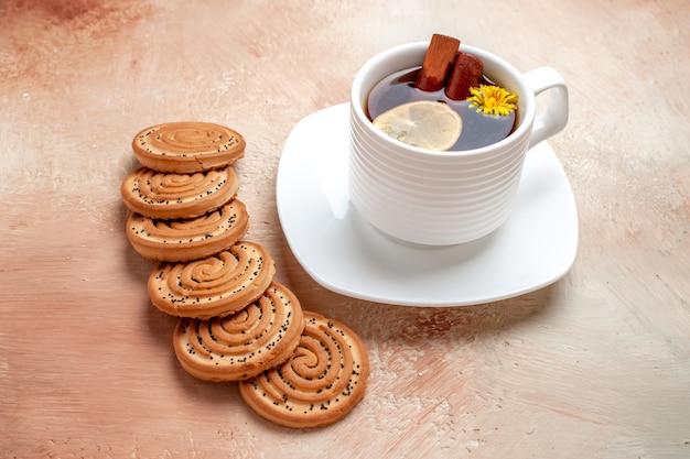 Xícara de chá de frente com biscoitos na mesa branca biscoito de chá de limão