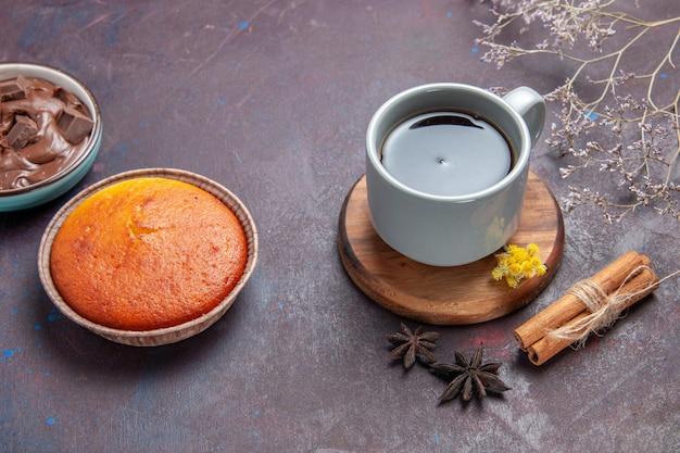 Xícara de chá de frente com bolo delicioso no fundo escuro bolo de chá torta doce biscoito biscoito