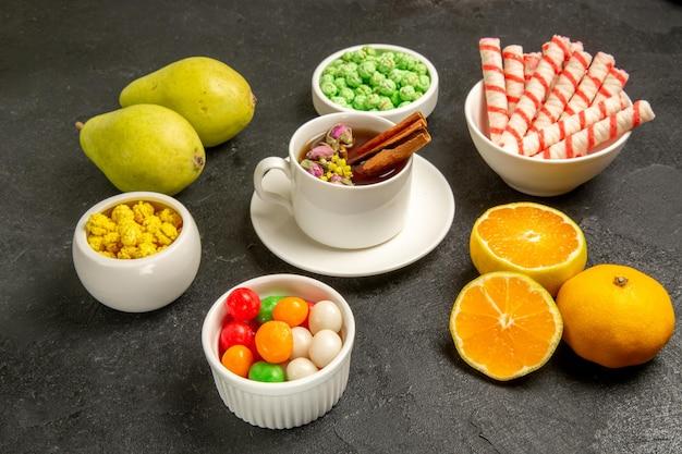 Xícara de chá de frente com doces e frutas frescas em um espaço cinza escuro