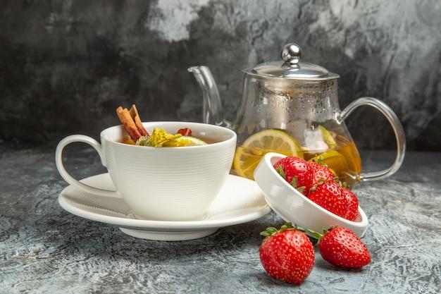 Xícara de chá de frente com morangos na superfície escura de frutas chá baga