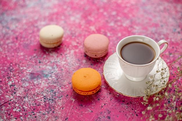 Xícara de chá de frente para dentro da xícara no prato com macarons franceses na mesa rosa