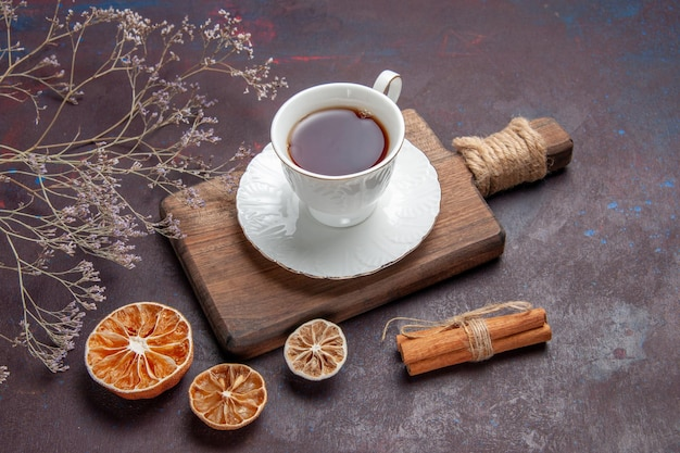 Xícara de chá de frente para dentro do copo de vidro com o prato na mesa escura.