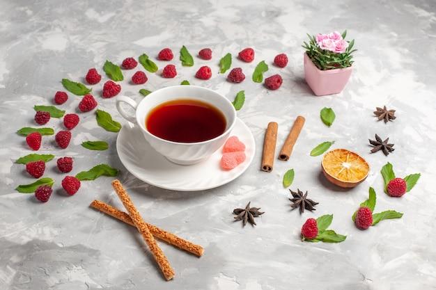 Xícara de chá de frente para o chá com canela e framboesas na superfície clara