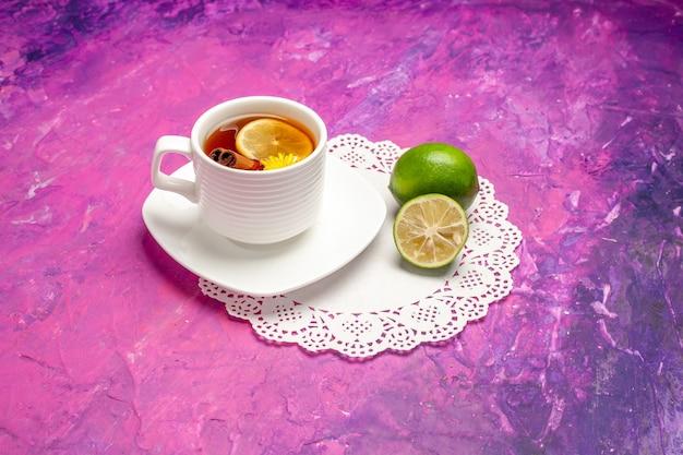Xícara de chá de frente para o chá com limões na mesa rosa cor doce chá limão