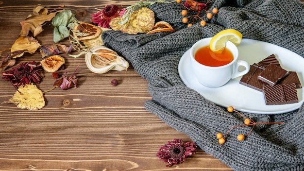 Xícara de chá de frutas com limão, chocolate no pires branco no pulôver quente. folhas e pétalas secas de outono