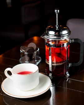 Xícara de chá de frutas e imprensa francesa em cima da mesa