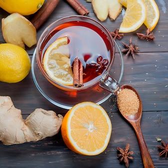 Xícara de chá de gengibre com limão e mel em fundo de madeira marrom escuro