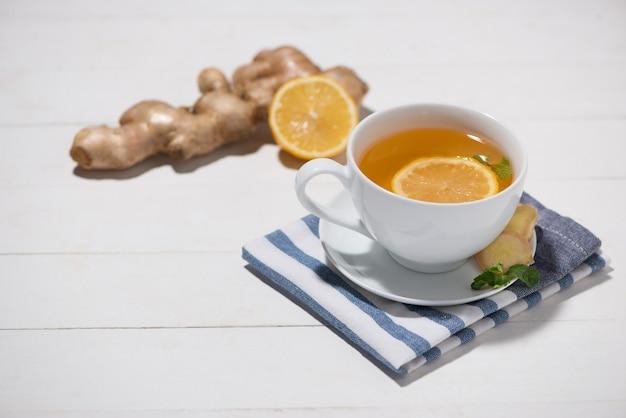 Xícara de chá de gengibre com limão e mel em um fundo branco de madeira.