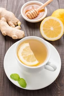 Xícara de chá de gengibre com limão e mel no fundo de madeira